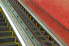 Escalator and red tiled wall Royalty Free Stock Photography