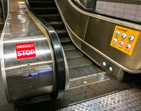 Escalator showing ` Emergency stop button ` and Caution Sign. An Escalator showing ` Emergency stop button ` and Caution Sign stock photo