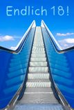 Escalator sky finally endlich 18 german. Escalator into a blue sky, concept of achievement, ENDLICH 18 german text, meaning FINALLY 18, adulthood and freedom Royalty Free Stock Photo