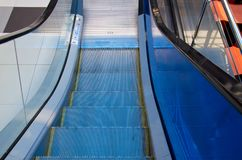 Escalator stairs down the blue handrail. In shopping centre stock photos