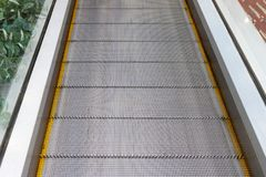 Escalator without stairs in a shopping mall. Moving down staircase. Close up metal platform. Top view Royalty Free Stock Images