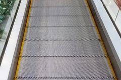 Escalator without stairs in a shopping mall. Moving down staircase. Close up metal platform. Top view Royalty Free Stock Photography