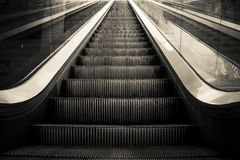 Escalator. Symmetrical view of a black and white escalator Royalty Free Stock Photography