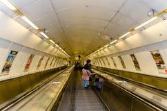 Escalator to Prague metro station. Couple reading advertising posters on an escalator down to the Prague Metro Stock Photography