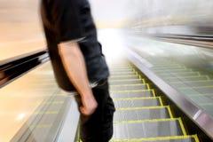 Escalator Toward the Light. Man descending an escalator toward bright light Stock Photos