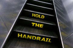 Escalator with yellow hold the handrail warning Royalty Free Stock Images