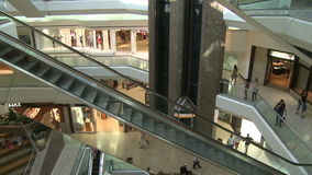 Escalators ascending while elevator descends within mall. A view or scene of Shopping stock footage