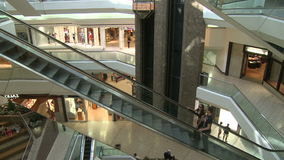 Escalators ascending with people while elevator descends within mall (1 of 2). A view or scene of Shopping stock video footage