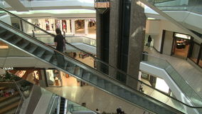 Escalators ascending with people while elevator descends within mall (2 of 2). A view or scene of Shopping stock footage