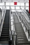 Escalators in big modern area. No people around. Grey tones interior design with shiny glass. Perspective front vertical view. Na stock image