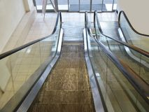 Escalators from the ground floor to the second one inside a supermarket, top-down view. The walls are painted in a light yellow color. Sliding glass doors lead Stock Images
