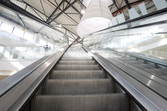 Escalators in mall. Bright interior of empty shopping mall with escalators Stock Photos