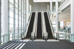 Escalators in an office building. Front view of escalators in an empty modern office building stock photo