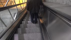 Escalators and people goto subway. A moving staircase consisting of an endlessly circulating belt of steps driven by a motor, conveying people between the stock video
