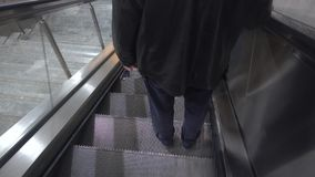 Escalators and people goto subway. A moving staircase consisting of an endlessly circulating belt of steps driven by a motor, conveying people between the stock video footage