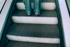 Escalators. Stairs, escalators, legs men knee standing on the ladder, iron, hoisting machine,in subways Royalty Free Stock Photography