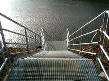 Escalera al lado de un río Foto de archivo