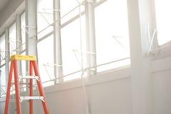 Escalera anaranjada en el vestíbulo blanco de la ventana imágenes de archivo libres de regalías