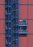 Escalera azul del metall en el edificio industrial rojo fotos de archivo