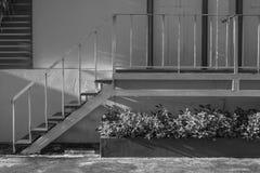 Escalera blanca de la vista lateral pequeña que sube a la puerta imágenes de archivo libres de regalías