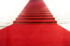 Escalera con la alfombra roja, iluminada por la luz Imágenes de archivo libres de regalías