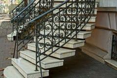 Escalera con pasos concretos grises y barandillas negras del hierro con un modelo forjado cerca de la pared en la acera fotografía de archivo