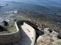 Escalera concreta abajo al mar Pendiente espiral de las escaleras al agua Toscana, Italia Fotografía de archivo libre de regalías