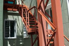 Escalera de acero roja por la pared verde foto de archivo