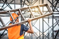 Escalera de aluminio que lleva del trabajador asiático joven del mantenimiento imagen de archivo libre de regalías
