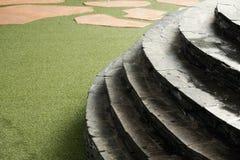 Escalera de la piedra y de la curva en césped artificial y piedra marrón fotos de archivo