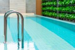 Escalera de las barras de gancho agarrador en la piscina azul, la piscina con la escalera y la cubierta de madera en el hotel fotografía de archivo libre de regalías