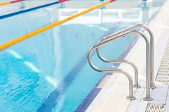 Escalera de las barras de gancho agarrador para los nadadores en la piscina imagenes de archivo