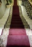 Escalera de mármol con una alfombra roja que lleva fotografía de archivo libre de regalías