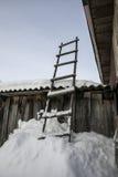Escalera de madera Colocación en la nieve acumulada por la ventisca El inclinarse contra el granero w Fotografía de archivo