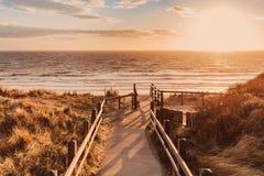 Escalera de madera en la luz de la tarde con vistas al mar Foto de archivo