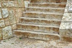 Escalera de madera vieja y pared de piedra Foto de archivo libre de regalías