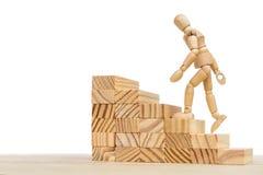 Escalera de madera y muñeca de madera contra el fondo blanco con el espacio libre para más lejos corregir fotos de archivo libres de regalías