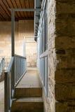 Escalera de piedra que lleva a un paso estrecho enmarcado por las puertas y la barandilla de madera azules Foto de archivo
