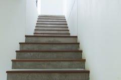 Escalera del cemento y de madera en la pared blanca del mortero Imagenes de archivo