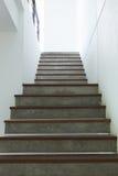 Escalera del cemento y de madera en la pared blanca del mortero Imagen de archivo