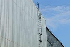 Escalera del hierro largo en una pared gris del metal de un edificio industrial contra el cielo fotos de archivo libres de regalías