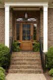 Escalera del ladrillo que lleva a una puerta principal marrón Foto de archivo