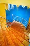 Escalera espiral colorida con el piso azul fotografía de archivo