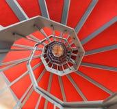 Escalera espiral con la alfombra roja en un edificio Fotos de archivo