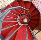 Escalera espiral con la alfombra roja en un edificio moderno Foto de archivo