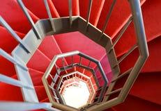Escalera espiral moderna con la alfombra roja Foto de archivo