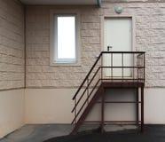 Escalera a la puerta trasera contra la pared modelada y a la mofa encima de ventanas Foto de archivo