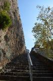 Escalera larga hacia el cielo cerca de la pared de piedra Foto de archivo libre de regalías