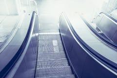 Escalera móvil, arriba y abajo de las escaleras móviles en el edificio público o el subterráneo Foto de archivo libre de regalías