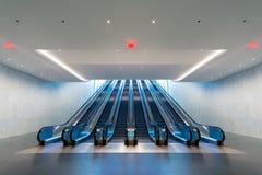 Escalera móvil con la luz azul que viene de arriba Imágenes de archivo libres de regalías
